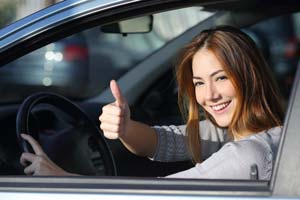 Teen female student driver with thumb up
